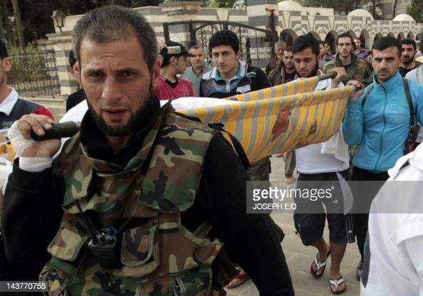 Free Syrian Army members from the alFaruq Brigade carry the body of one of their comrades to the Khaled Ibn alWalid mosque for his funeral in the...