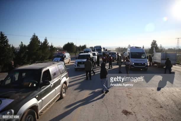 Free Syrian Army members take security measures as arrival of a convoy carrying approximately 500 Syrian civilians evacuated from AlWaer neighborhood...