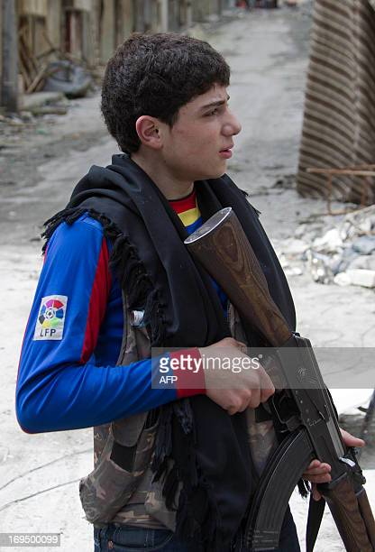 A Free Syrian army's young fighter holds a position during clashes with regime froces on March 31 2013 in the northern Syrian city of Aleppo AFP...