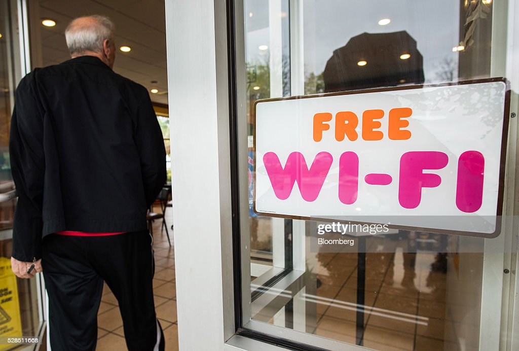 A 'Free Wi-Fi' sign is displayed in the window as a customer enters a Dunkin' Donuts Inc. location in Ramsey, New Jersey, U.S., on Thursday, May 5, 2016. Dunkin' Brands Group Inc., a leading franchiser in the quick service restaurants (QSR) sector, operates in almost 60 countries around the world with more than 11,300 Dunkin' Donuts restaurants and 7,500 Baskin-Robbins locations. Photographer: Ron Antonelli/Bloomberg via Getty Images
