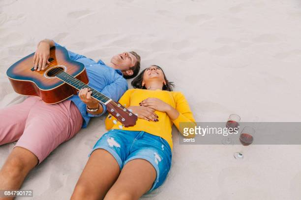 Free young couple lying down in the sand beach