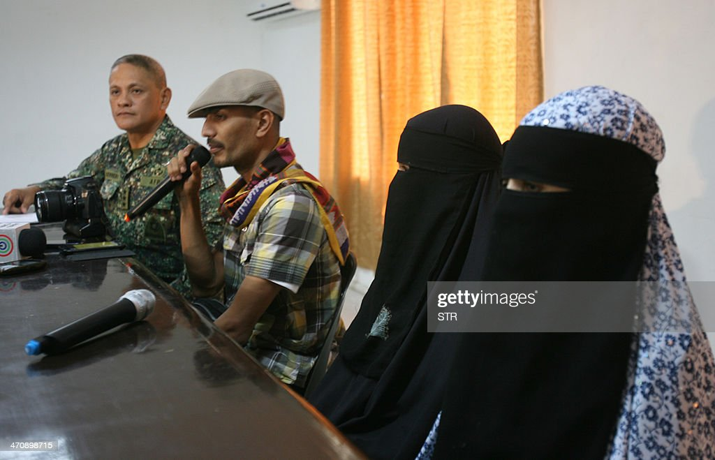 Freed captive Filipino-Algerian sisters Nadjoua and Linda Bansil clad in masturah and nijab veils are presented by their brother Mohammed Bansil (2nd-L) with military chief, Lieutenant General Rustico Guerrero (L) during a briefing in a military camp in Zamboanga City, southern Philippines on February 21, 2014. The two Filipina documentary film-makers, kidnapped by Al-Qaeda-linked Muslim extremists in the strife-torn southern Philippines, were recovered by authorities on February 21 after eight months in captivity, a military statement said.