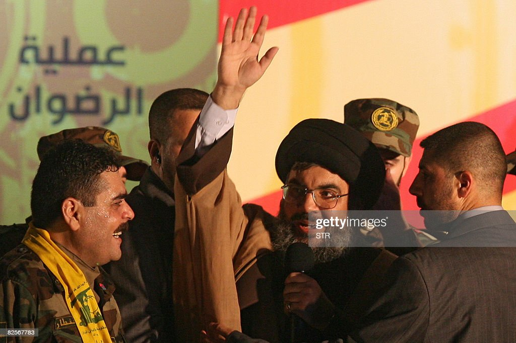 Freed Lebanese prisoner Samir Kantar (L) smiles as Hezbollah chief Hassan Nasrallah (C) waves to the crowd upon his arrival to greet freed Lebanese prisoners during celebrations at a stadium in Beirut's southern suburb on July 16, 2008. Nasrallah appeared in person today at public celebrations for the release of five Lebanese prisoners from Israel in the southern suburbs of Beirut. Nasrallah hailed the 'victory' of his movement in the swap, which saw the five Lebanese prisoners exchanged for the bodies of two Israeli soldiers Hezbollah had captured in a cross-border raid in 2006 -- Eldad Regev and Ehud Goldwasser. AFP PHOTO/STR