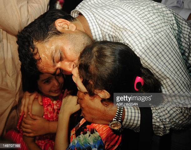 Freed Pakistani crew member of a Malaysiaowned ship seized by the Somali pirates kisses his children upon his arrival in Karachi on August 2 2012...