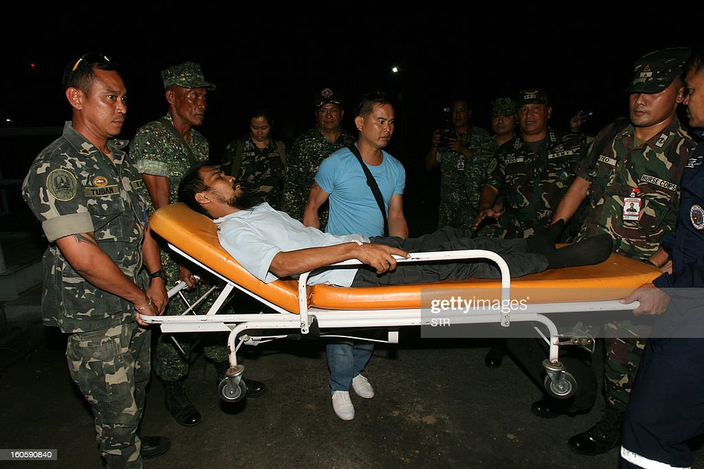 Freed Philippine hostage, cameraman Ramil Vela (C) is carried on a stretcher by military personnel shortly after arrrving from Jolo town, at the port in Zamboanga city, in southern island of Mindanao on February 3, 2013, hours after he walked free from Islamist Abu Sayyaf militants. Militants have freed two Filipino television crew members seized along with a Jordanian journalist nearly eight months ago in the southern Philippines, police said February 3.
