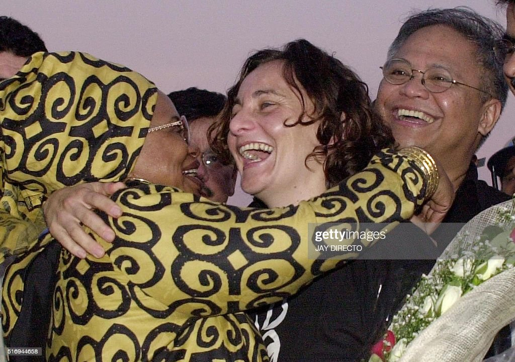 Freed South African hostage Monique Strydom receives a hug from South African ambassador Lindiwe Mabuza while Philippine chief negotiator Robert...