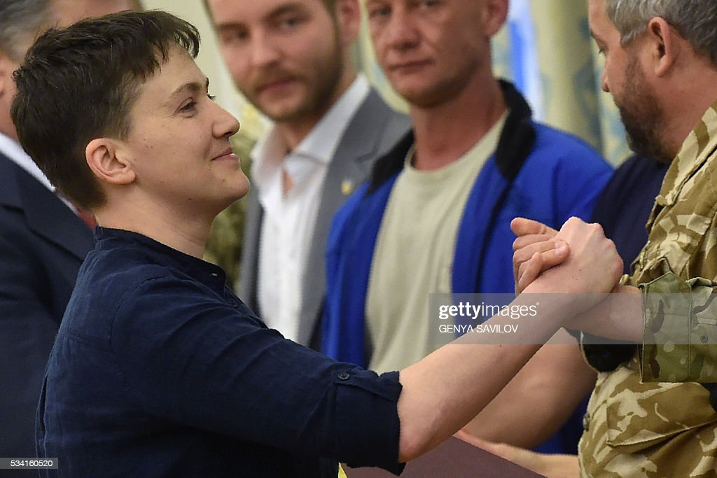 Freed Ukrainian pilot Nadiya Savchenko shakes hands with servicemen from the Aydar battalion during a meeting with Ukraine's President in Kiev on May 25, 2016. Ukrainian pilot Nadiya Savchenko returned home to a hero's welcome on May 25 after nearly two years in a Russian prison, drawing a line under a damaging diplomatic spat between Moscow and Kiev. The 35-year-old army helicopter pilot flew home as part of an apparent prisoner swap with Moscow, with two alleged Russian soldiers leaving Ukraine earlier in the day. / AFP / GENYA