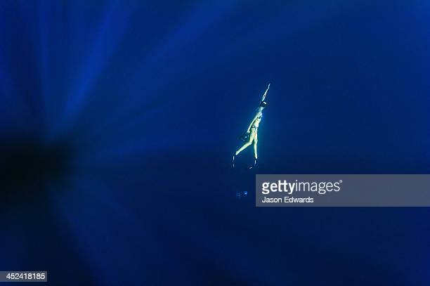 A free-diver swims through sun rays in the vast ocean depths.