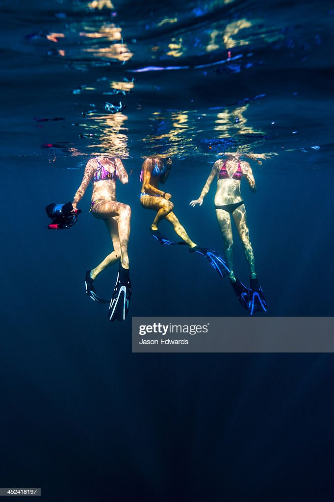 Free-divers in bikinis float on the ocean surface with a video camera. : Stock Photo