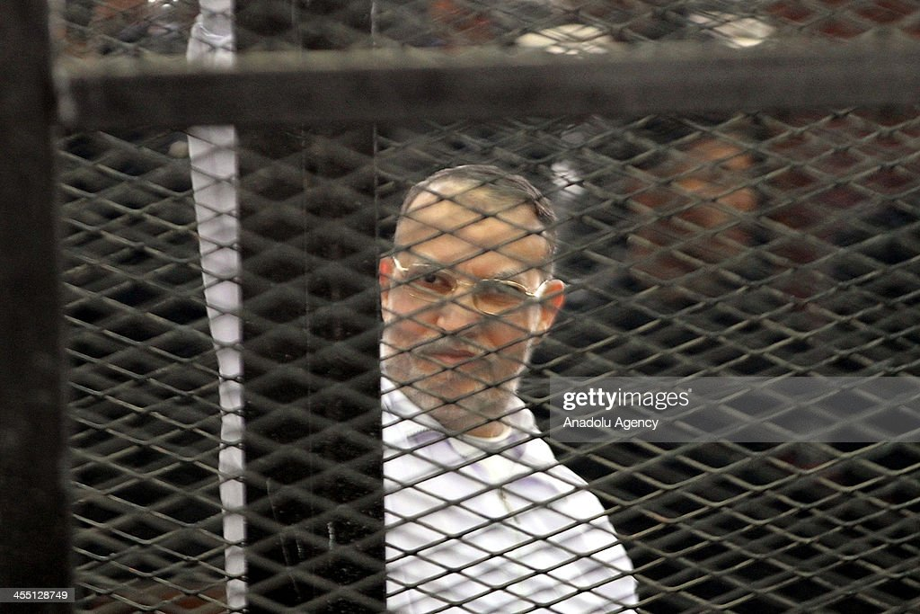 Freedom and Justice Party (FJP) deputy leader Essam al-Erian gestures behind bars during the trial of Brotherhood members at a courtroom on December 11, 2013 in Cairo, Egypt. For the second time, judges presiding over the trial of Muslim Brotherhood leader Mohamed Badie and 18 other defendants withdrew from trial proceedings on Wednesday. The defendants are accused of inciting the murder of anti-Brotherhood protesters during June 30 clashes between supporters and opponents of ousted president Morsi outside the Brotherhood's Cairo headquarters.