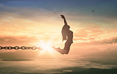 Silhouette of a girl jumping and broken chains at sunset meadow with her hands raised
