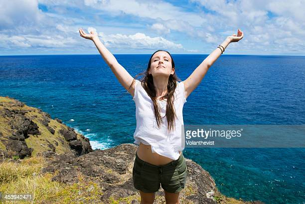 Freedom. Girl with arms raised on a cliff w/ sea