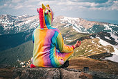 Female hiker in a unicorn suit meditating on top of the mountain on a Carpathian landscape background on a Spring day. Wanderlust travel concept.