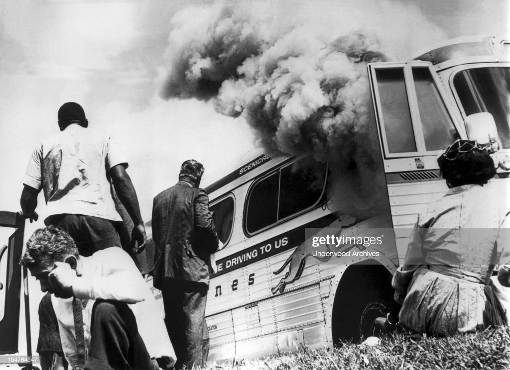 Freedom Riders on a Greyhound bus sponsored by the Congress Of Racial Equality (CORE), sit on the ground outside the bus after it was set afire by a group of whites who met the Negro and white group on arrival here, Anniston, Alabama, May 14, 1961. After