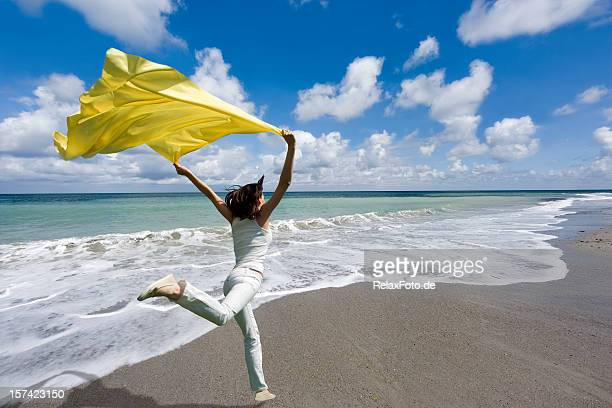 Freedom - Woman jumping seaside holding yellow scarf in wind