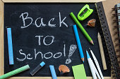 Freehand writing Back to school letters on chalkboard with School supplies