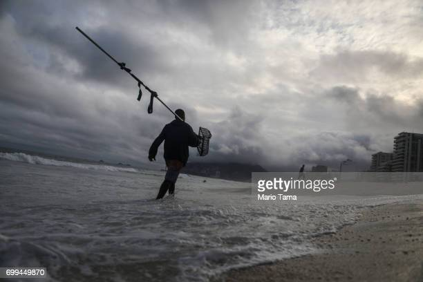 Freelance beach prospector Luis Fernando carries a sifting device which he uses to search for items lost and buried in the sand on June 21 2017 in...