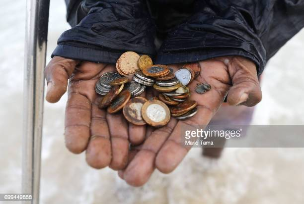 Freelance beach prospector Luis Fernando displays coins he found today buried in the sand on June 21 2017 in Rio de Janeiro Brazil He says he...