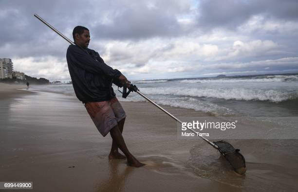 Freelance beach prospector Luis Fernando manuevers a sifting device which he uses to search for items lost and buried in the sand on June 21 2017 in...