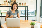 Freelance Businesswoman drinking coffee and using tablet computer in  coffee shop