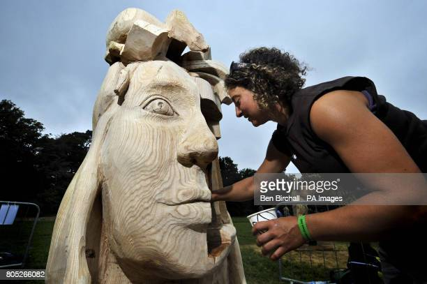 Freelance chainsaw carver Mandy Schmidt begins the finishing touches as she brushes Norwegian oil onto her wood sculpture of the fictional character...