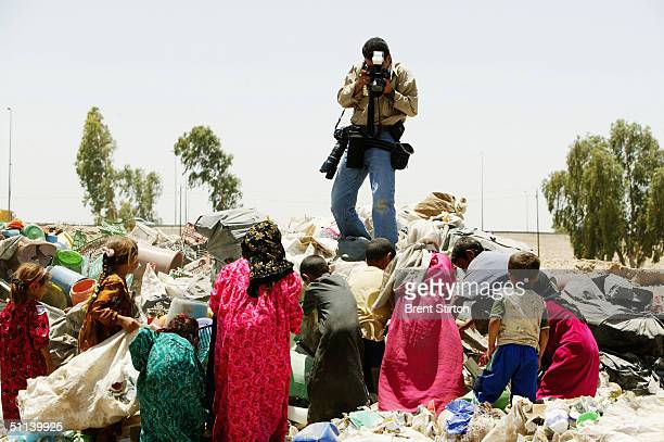 Freelance Iraqi photographer Wathiq Khuzaie working for Getty Images shoots a photograph of poor Iraqis who live amongst the garbage dumps June 30...