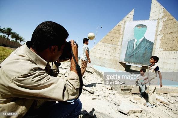 Freelance Iraqi photographer Wathiq Khuzaie working for Getty Images photographs boys playing football in front of a defaced mural of Saddam Hussein...