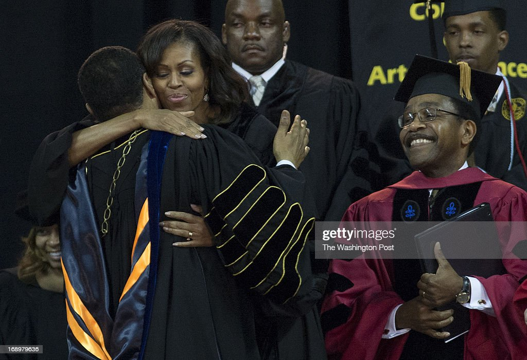 Freeman A. Hrabowski, III, receives a hug from First Lady Michelle Obama as Dr. Weldon Jackson, Provost and Vice President of Academic Affairs, right, looks on during the 2013 Spring Commencement ceremony at Bowie State University held at the University of Maryland's Comcast Center in College Park, Maryland, on Friday, May 17, 2013. Mrs. Obama received an Honorary Doctorate of Laws degree.