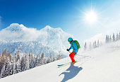 Free-ride skier in fresh powder snow running downhill in beautiful Alpine landscape. Blue sky on background. Free space for text