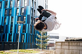 Freerunner is doing a flip from a wall in the city.