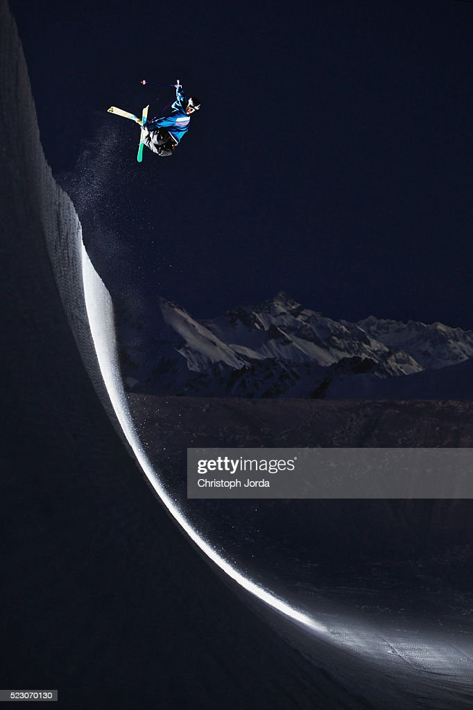 Freestyle skier jumping in a halfpipe in the mountains at night