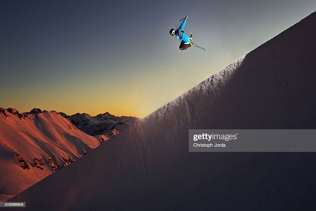 Freestyle skier jumping in a halfpipe in the mountains