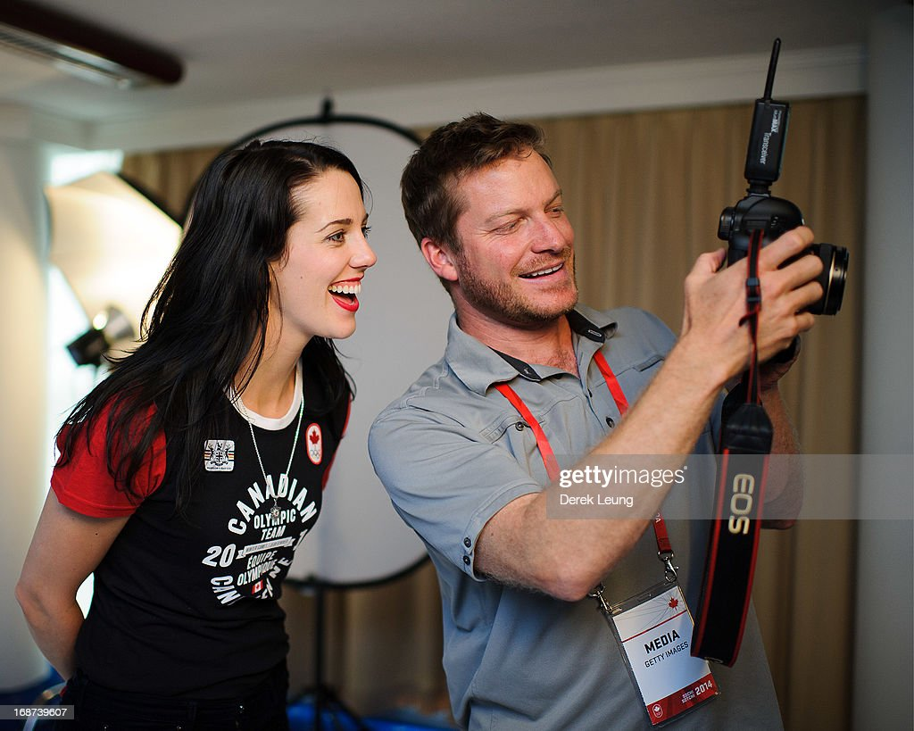 Freestyle skier Rosalind Groenewoud smiles as she reviews her photos taken by photographer Jonathan Ferrey (R) during the Canadian Olympic Committee Portrait Shoot on May 13, 2013 in Vancouver, British Columbia, Canada.