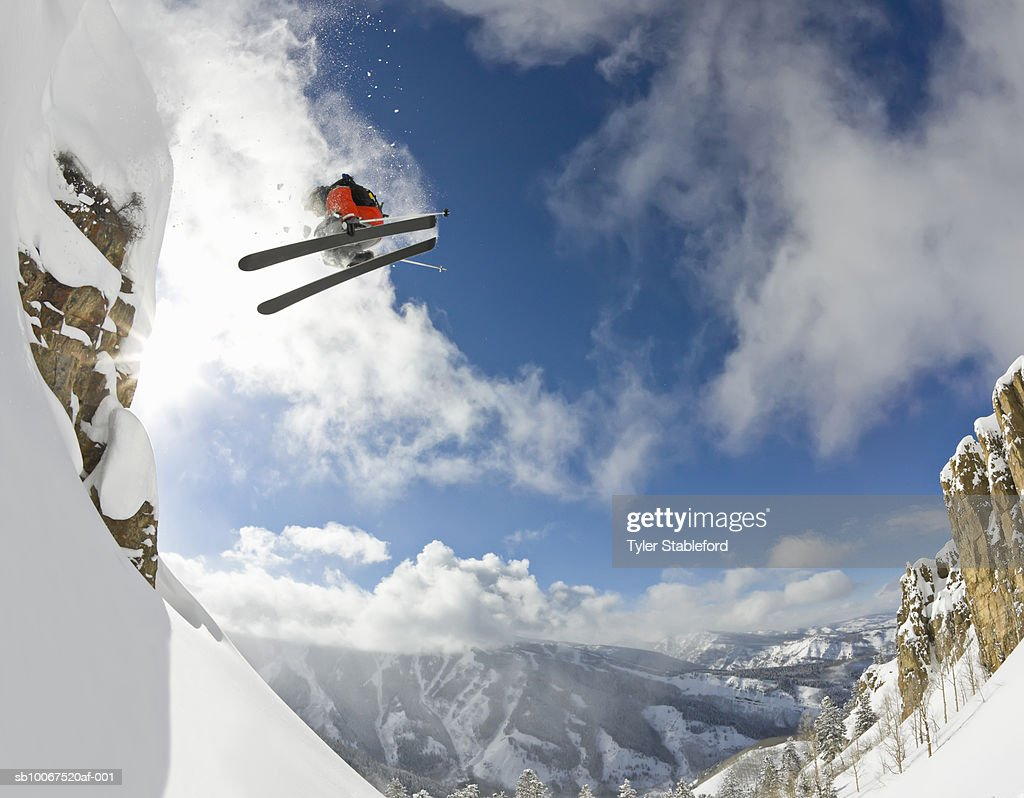 Freestyle skier spinning while jumping off of cliff