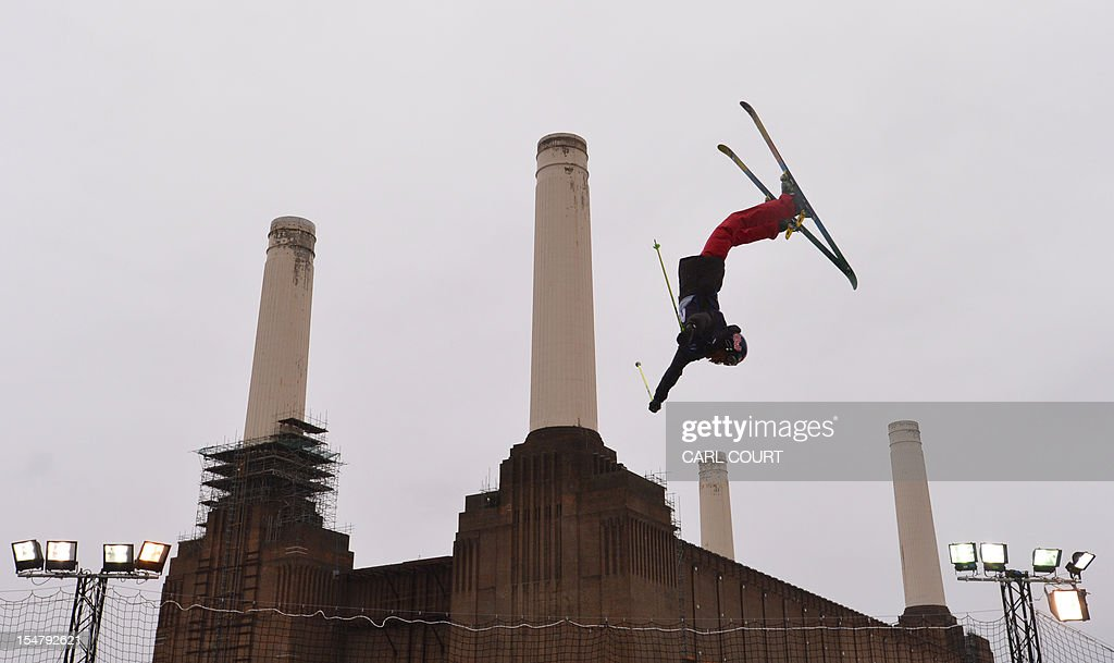 A freestyle skier twists through the air in front of Battersea Power Station during the Relentless Freeze winter sports freestyle skiing competition in London on October 26, 2012.