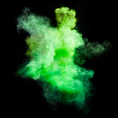 Freeze motion of green dust explosion isolated on black background