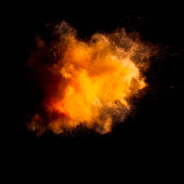 Freeze motion of yellow dust explosion isolated on black background