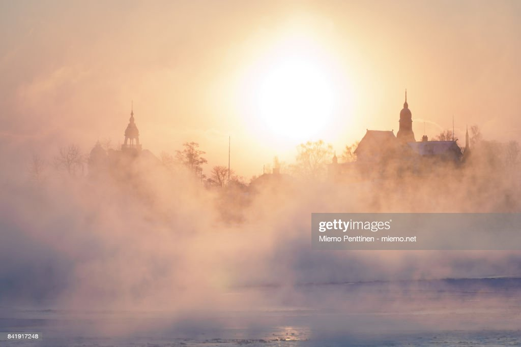sun coming up behind the mist rising from the frozen sea