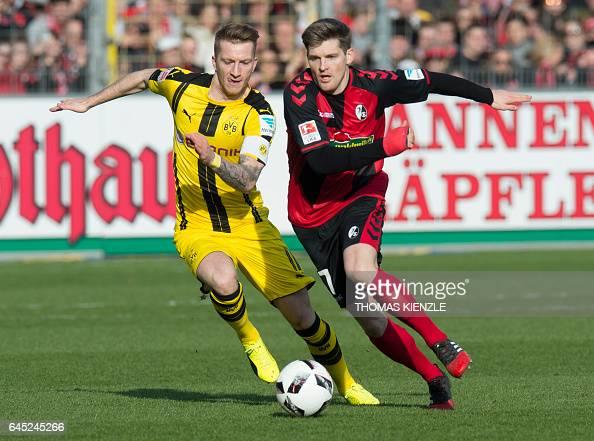 TOPSHOT Freiburg's defender Lukas Kuebler and Dortmund's midfielder Marco Reus vie for the ball during the first German division Bundesliga football...