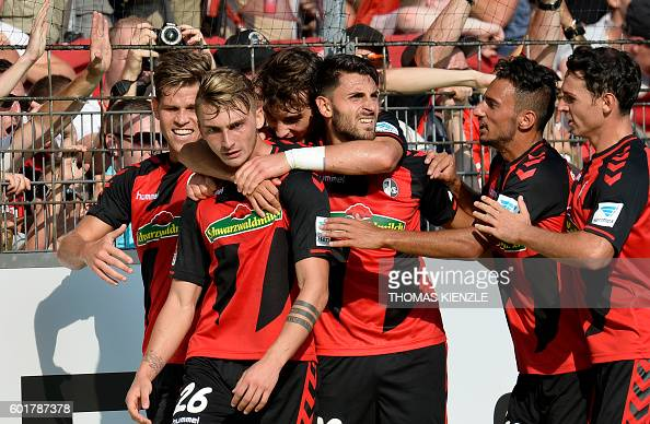 Freiburg's forward Maximilian Philipp is congratulated by teammates after he scored during German first division Bundesliga football match between SC...