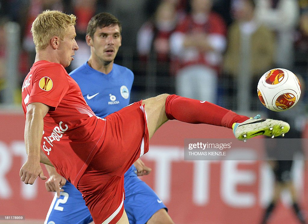 Freiburg's forward Mike Hanke (L) and Liberec's Croatian defender Renato Kelic vie for the ball during Europa league football match between SC Freiburg vs FC Slovan Liberec in Freiburg on September 19, 2013.