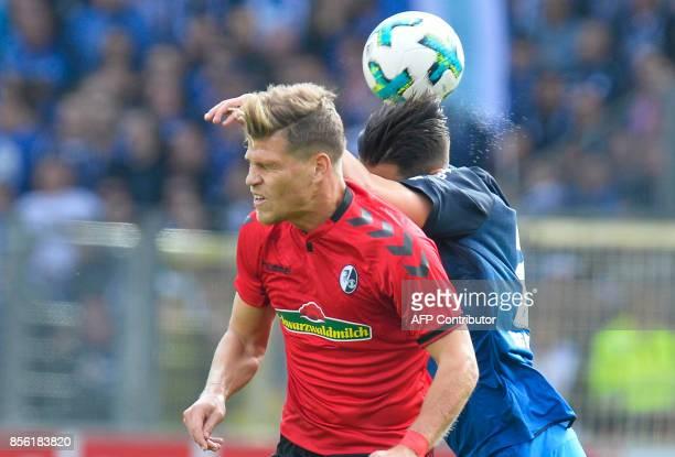 Freiburg's German forward Florian Niederlechner and Hoffenheim's German defender Benjamin Huebner vie for the ball during the German first division...