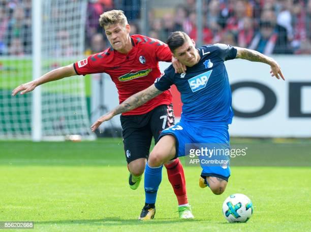 Freiburg's German forward Florian Niederlechner and Hoffenheim's German midfielder Steven Zuber vie for the ball during the German first division...