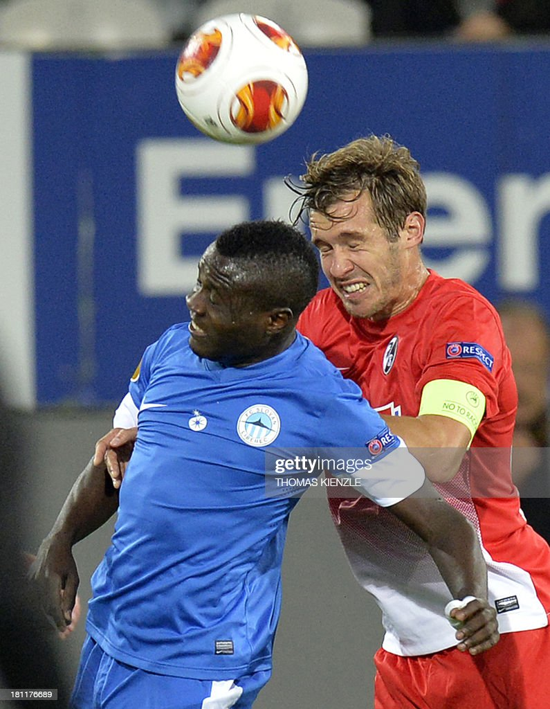 Freiburg's midfielder Julian Schuster (R) vies with Liberec's Congolese forward Dzon Delarge during Europa league football match between SC Freiburg vs FC Slovan Liberec in Freiburg on September 19, 2013.