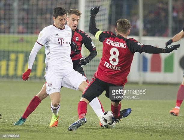 Freiburg's midfielder Mike Frantz and midfielder Janik Haberer vie for the ball with Munich's Polish forward Robert Lewandowski during the German...