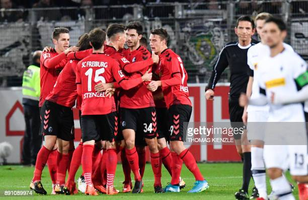 Freiburg's players celebrate next to referee Deniz Aytekin after forward Nils Petersen scored the opening goal during the German first division...