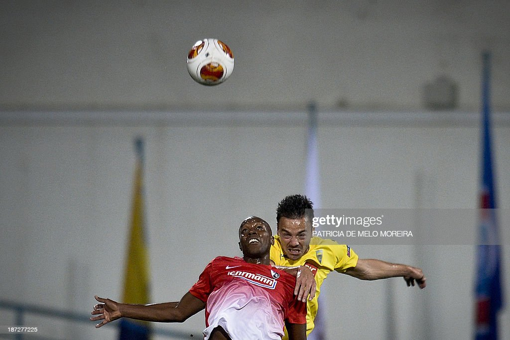 Freiburg's Slovenian midfielder Karim Guede (L) heads the ball as he vies with Estoril's defender Yohan Tavares (R) during the UEFA Europa League group H football match Estoril vs SC Freiburg at the Antonio Coimbra da Mota stadium on November 7, 2013.
