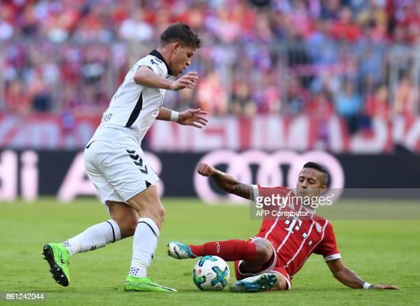 Freiburg's striker Florian Niederlechner and Bayern Munich's Spanish midfielder Thiago Alcantara vie for the ball during the German First division...