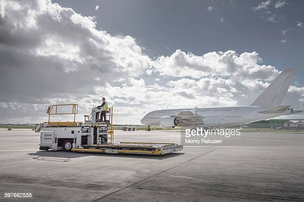 Freight handling machine with A380 aircraft on runway