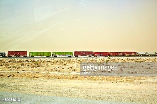 Freight locomotive moving through arid landscape, California, USA